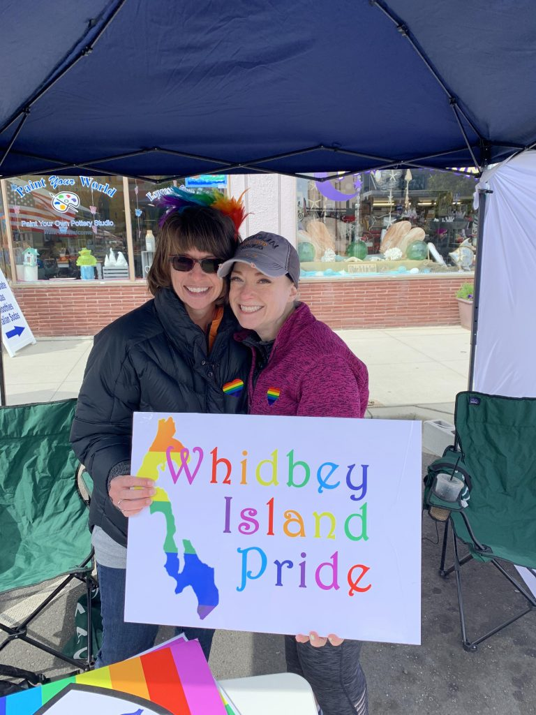Anita Johnston  Windermere Real Estate agent at Oak Harbor Holland Happening Event with Pride Booth.  Anita was taking pictures , handing out rainbow flags, love sticker and free hugs.  Sharing the love.